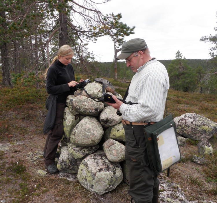"The boundary marker in Puntarikero, or the Pikku-Palotunturi Fell in Posio, is mentioned in many historical sources as marking the boundary between Kemi and Tornio, and the border between Lapland and ""Lanta"", the rest of Finland. Trainee Inga Nieminen and forestry worker Timo Simontaival documenting the boundary marker. Photo: Taisto Karjalainen/Metsähallitus."
